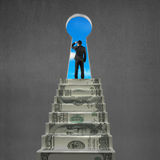 Man looking on top of money stairs with key hole Royalty Free Stock Photo