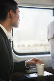 Man Looking Through Train Window While Stirring His Coffee Stock Photos