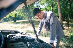 Man looking under the hood of car Royalty Free Stock Images