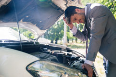 Man looking under the hood of car. Man in suit looking under the hood of breakdown car outdoors Royalty Free Stock Photos