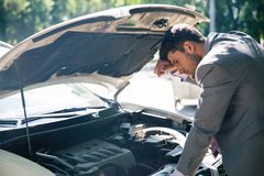 Man looking under the hood of car. Young man looking under the hood of breakdown car Stock Images