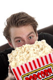 Man looking up from behind a popcorn bucket Stock Image