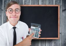 Man looking up with calculator against chalkboard and grey wood panel. Digital composite of Man looking up with calculator against chalkboard and grey wood panel Stock Photography
