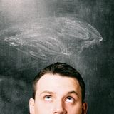 Man is looking up. With chalk board behind him Royalty Free Stock Images
