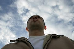 Man Looking up with the Clouds on the Background. Man Looking up with the Clouds and the Blue Skies on the Background Royalty Free Stock Images