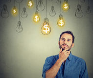 Man looking up with dollar idea light bulb above head. Portrait thinking handsome young man looking up at many dollar idea light bulbs above head Stock Photo