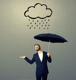 Man looking up at drawing storm cloud Stock Images