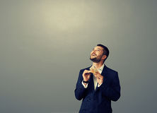 Man looking up at empty dark copyspace. Smiley businessman counting money and looking up at empty dark copyspace Stock Images