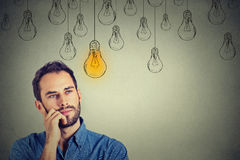 Man looking up with idea light bulb above head. Portrait thinking handsome man looking up with idea light bulb above head  on gray wall background Royalty Free Stock Photography