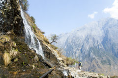 Man Looking Up at Mountainside Waterfall Stock Photo
