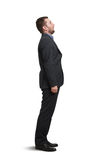 Man looking up with open mouth. Full-length portrait of amazed man in black suit looking up with open mouth. isolated on white background Royalty Free Stock Photography