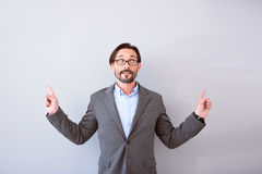 Man looking up and pointing with hands. I will show you. Bearded confident mature man looking up and pointing with hands while talking and standing isolated on Royalty Free Stock Images