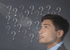 Man looking up at question marks. Digital composite of man looking up at question marks Stock Photos