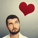 Man looking up at red heart. Thoughtful man looking up at red heart over grey background Stock Photo