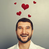 Man looking up at red hearts. Happy laughing man looking up at red hearts above his head over grey background Stock Photo