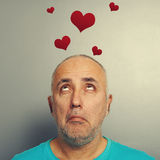 Man looking up at small red hearts Stock Photo