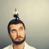 Man looking up at small successful man. Surprised man looking up at small successful man on the head Stock Photo