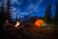 Man looking up at the stars next to campfire and tent at night. Man looking up at stars next to campfire and tent at night Royalty Free Stock Photos