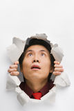 Man looking up surprisingly from hole in wall Royalty Free Stock Photo