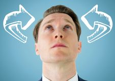 Man looking up at white curved arrows against blue background stock image
