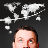 Man is looking up. At world map shaped clouds Stock Photo