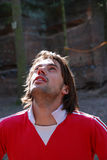 Man looking upwards. A portrait of a young man wearing a red pullover shirt, looking upwards to the top of rocks he is preparing to climb Stock Photos