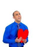 Man looking upwards, holding red heart to chest daydreaming of women in love Royalty Free Stock Photo