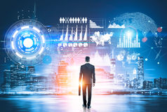 Man looking at virtual business panel. Back view of businessman holding briefcase in night city with hi-tech business panel. Virtual technology concept Stock Photos