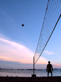Man looking at  volleyball. Area is in Sentosa Island, Singapore. The sunset was colourful and this man were having a game of volleyball. Picture was taken to Stock Photography