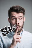 Man is looking wary. Over gray background. Man wearing a blue shirt is looking wary and saying Shh. Over gray background Stock Images