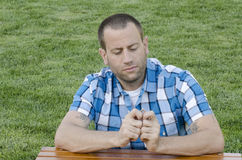 Man looking at a wedding ring. Man looking at his wedding ring outside on the grass while resting his arms on a table wearing a plaid shirt with a focused look Stock Image