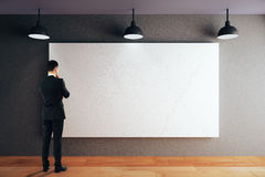 Man looking at whiteboard. Thoughtful businessman looking at blank whiteboard on black concrete wall in room with wooden floor and ceiling with lamps. Mock up Royalty Free Stock Photo