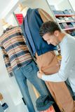 Man looking at width trouser leg on mannequin Royalty Free Stock Image