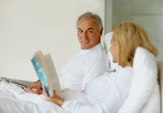 Man looking at wife while she reads a book in bed Royalty Free Stock Photo