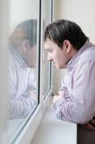 Man looking at the window. Courageous middle age man looking at the window Royalty Free Stock Image