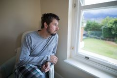 Man looking through the window. At home Stock Photo