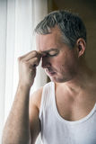 Man looking through window looking worried, depressed, thoughtful and lonely suffering depression in work Royalty Free Stock Images