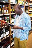Man looking at wine bottle in grocery section. At supermarket Stock Photo