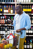 Man looking at wine bottle in grocery section. At supermarket Royalty Free Stock Image