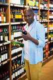 Man looking at wine bottle in grocery section. At supermarket Royalty Free Stock Photos