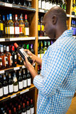 Man looking at wine bottle in grocery section. At supermarket Stock Images