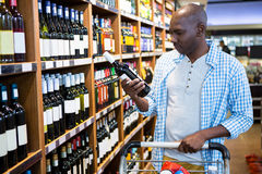 Man looking at wine bottle in grocery section. At supermarket Stock Photos