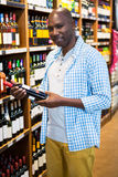 Man looking at wine bottle in grocery section at supermarket. Portrait of man looking at wine bottle in grocery section at supermarket Royalty Free Stock Image