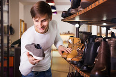 Man looking for a winer shoes in mall Stock Image