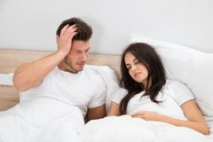 Man looking at woman snoring in bed. Upset Young Man Looking At Woman Snoring In Bed At Home Royalty Free Stock Photos