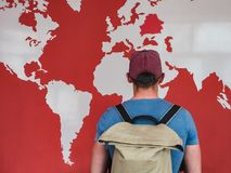 Man looking at the world map. Young man in a cap and glasses with a stylish, hiking backpack, looking at the countries and continents on the world map stock images