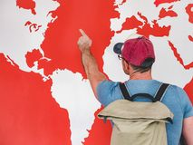 Man looking at the world map. Young man in a cap and glasses with a stylish, hiking backpack, looking at the countries and continents on the world map stock photography