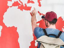 Man looking at the world map. Young man in a cap and glasses with a stylish, hiking backpack, looking at the countries and continents on the world map royalty free stock image