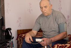 Man looking worried as he tests his blood pressure Royalty Free Stock Photo