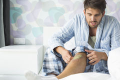 Man looking at wound on bed at home Royalty Free Stock Photo
